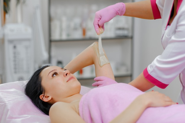 Professional woman making wax another woman in the arm