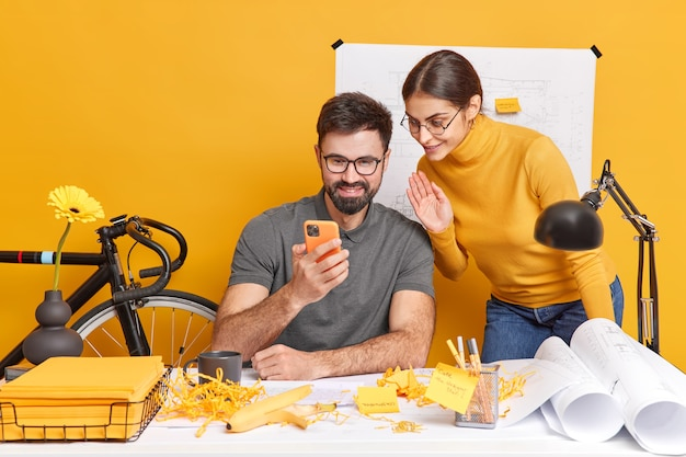 Professional woman and man colleagues enjoy online communication during work break work on construction project pose at desktop