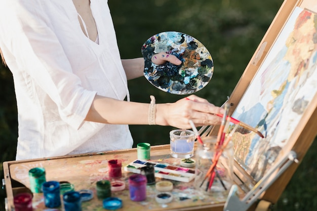 Professional woman painting in the nature