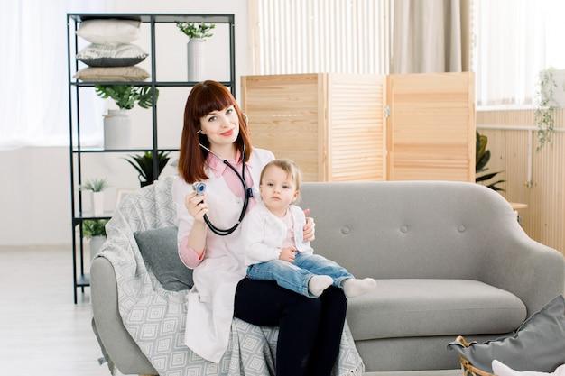 Профессиональная женщина педиатр, изучения маленькая девочка стетоскоп. доктор и ребенок, сидя на сером диване в современной клинике