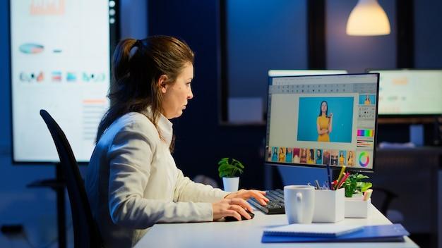 야간에 비즈니스 사무실에서 큰 프로젝트를 진행하는 전문 여성 사진 리터쳐. 성능 노트북, 아티스트, 직업, 화면, 그래픽을 사용하여 초상화 리터칭을 하는 콘텐츠 제작자