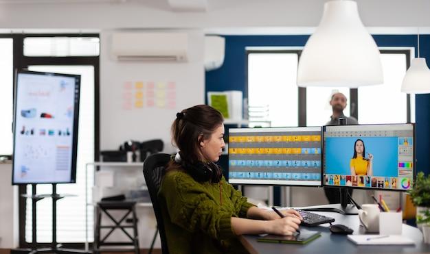 스타일러스 연필을 사용하여 창의적인 멀티미디어 회사에서 디지털 자산으로 작업하는 전문 여성 사진 리터쳐