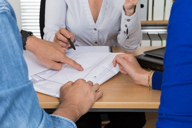 Professional woman receiving couple customer in her office