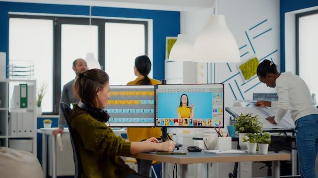 전문 여성 리터쳐가 크리에이티브 미디어 에이전시 사무실에서 자산을 편집합니다.