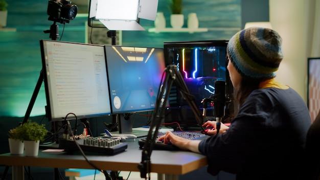 オンラインeスポーツトーナメント中にストリーミングチャットを介してマイクに向かって話しているfpsゲームをプレイするプロの女性ストリーマー。強力なコンピューターで新しいグラフィックを使用してオンラインビデオゲームを作成するゲーマー