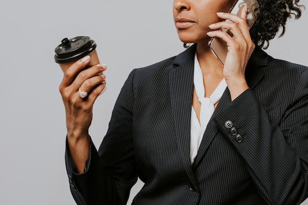 Professional woman with a coffee and a smartphone