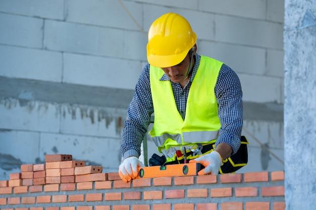 시멘트로 벽돌 벽을 구축하는 전문 작업자