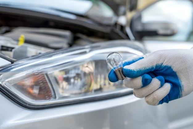 新しいハロゲン電球の車を交換するプロの労働者。自動修理
