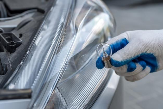 新しいハロゲン電球の車を変更するプロの労働者