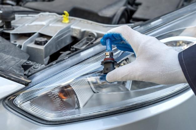 Профессиональный работник меняет новый автомобиль галогенных лампочек