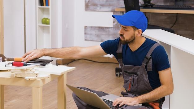 가구 조립에 적합한 도구를 노트북에서 확인하는 전문 작업자. 모자를 쓴 노동자.