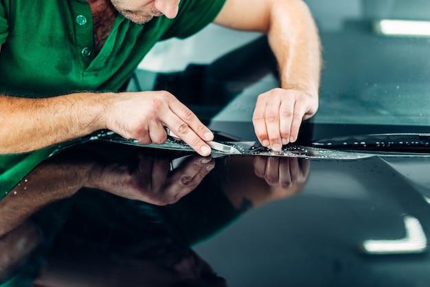 プロの労働者はペイントプロテクトをインストールします。欠けや傷に対する透明な保護フィルム。保護被膜