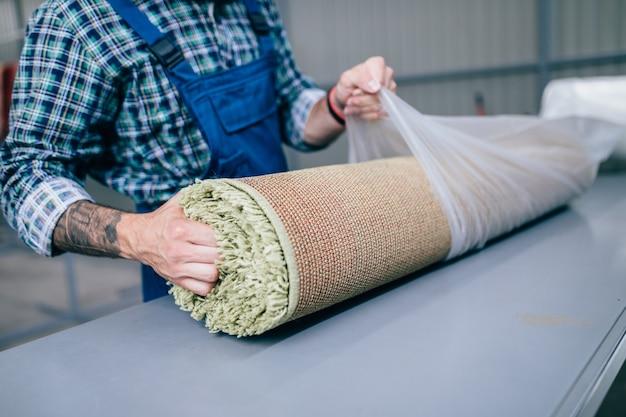 洗浄サービスできれいなカーペットを梱包するプロの労働者。