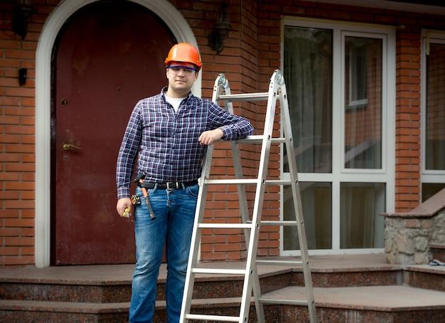 집 건물에 대 한 금속 사다리와 함께 포즈를 취하는 전문 작업자