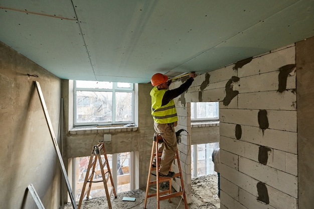 Professional worker standing on ladder and making measurements with tape measure to install drywall ceiling in highrise building under construction