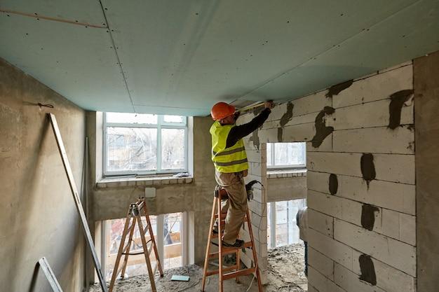 Профессиональный рабочий, стоящий на лестнице и производящий измерения с помощью рулетки, для установки потолка из гипсокартона в строящемся высотном здании