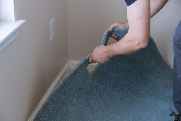 거실에서 리노베이션 작업을 위해 카펫을 제거하는 전문 작업자