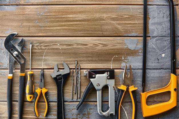 전문 워크숍 악기, 나무 테이블. 목수 도구, 빌더 장비, 스크루 드라이버 및 렌치, 말뚝 및 금속 가위, 쇠톱 및 스테이플러