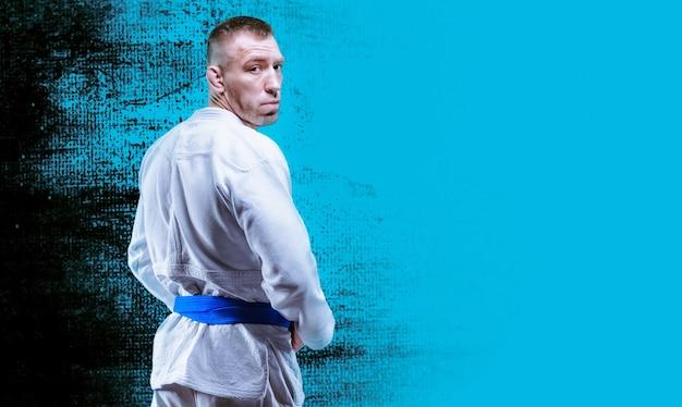 プロレスラーが着物を着ています。彼は肩越しに見ています。総合格闘技、空手、サンボ、柔道、柔術の概念。ミクストメディア