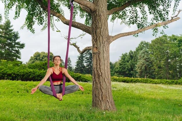 Профессиональная женщина йоги медленно дышит, выполняя сидящую позу воздушной йоги