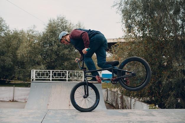 Профессиональный молодой мальчик-спортсмен-велосипедист с велосипедом bmx в скейтпарке