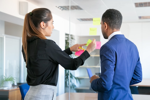 Professional young colleagues working with stickers. focused female worker sticking note on glass. focused businessman in blue suit standing near her. teamwork, business and collaboration concept