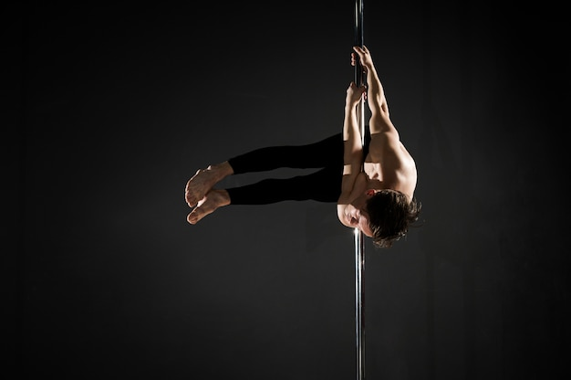 Professional young male model pole dancing
