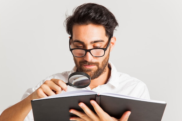 Professional young man reading with loupe and glasses