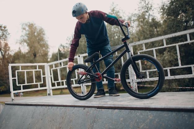 Профессиональный молодой человек-спортсмен-велосипедист проверяет давление в колесных шинах на велосипеде bmx в скейтпарке