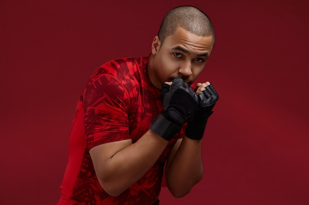 Professional young mixed race kickboxer in training outfit exercising in studio, practicing punches, standing in defensive posture with hands at his face. boxing, kickboxing and martial arts concept