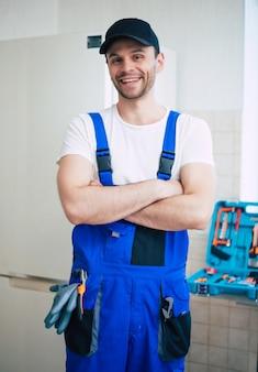 부엌에서 냉장고 수리 후 장비와 현대 도구 상자와 작업자 유니폼 및 모자 전문 젊은 수리공