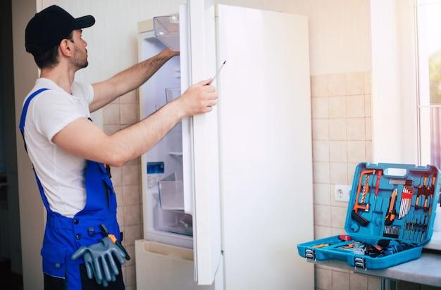 장비와 현대 도구 상자와 작업자 유니폼 및 모자 전문 젊은 수리공이 부엌에서 냉장고를 수리하고 있습니다