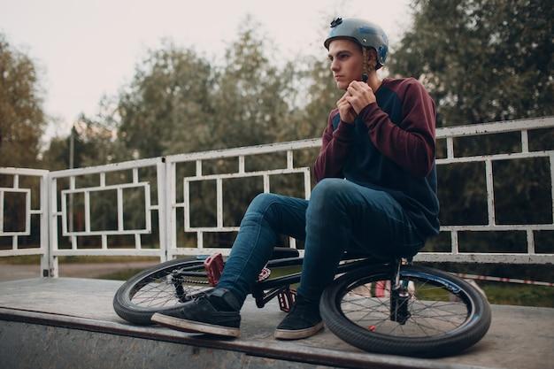 Профессиональный молодой спортивный велосипедист с велосипедом bmx в скейтпарке