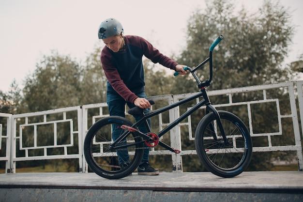 Профессиональный молодой спортсмен-велосипедист с велосипедом bmx в скейтпарке.