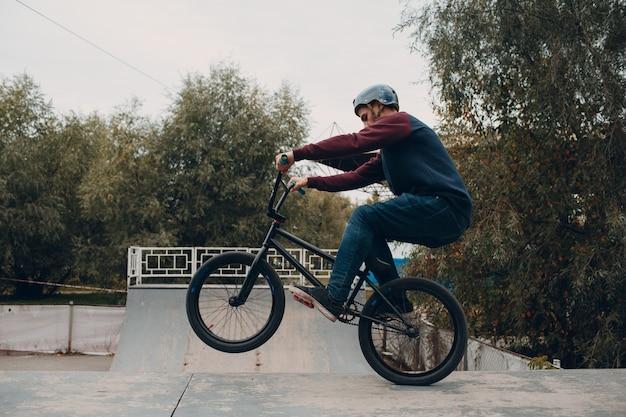Профессиональный молодой спортсмен-велосипедист с велосипедом bmx в скейтпарке