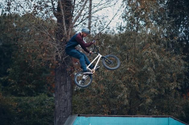 Профессиональный молодой спортсмен-велосипедист с велосипедом bmx делает трюк в скейтпарке