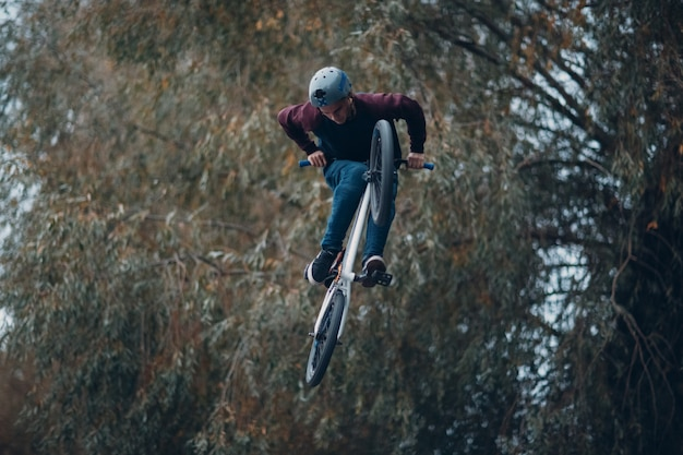 Professional young sportsman cyclist with bmx bike making acrobatic trick  at skatepark. young man bmx biker,