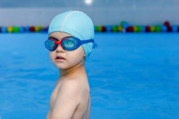 Профессиональный молодой пловец в синей кепке готов плавать в воде бассейна.