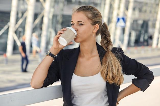通りに立ってコーヒーを飲むプロの若い都会のカジュアルなビジネス女性