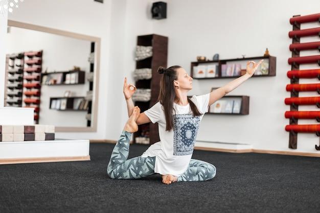 マットの上のフィットネスルームでエクササイズをしているプロの若い女性。スポーティな女の子は、ヨガ、ストレッチ、ピラティスの練習をします。