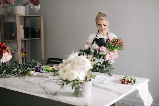 테이블에 신선한 튤립으로 꽃꽂이를 만드는 앞치마를 입은 전문 젊은 여성 꽃집