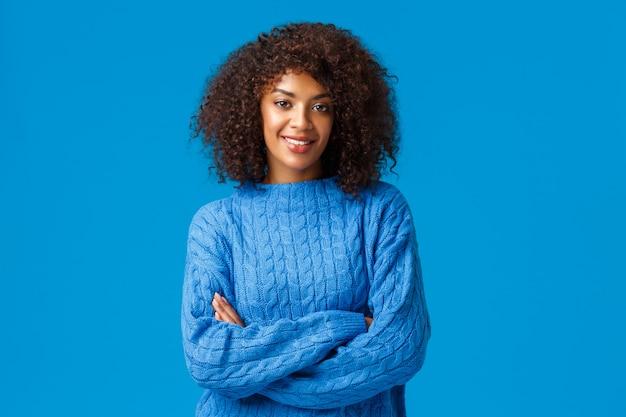 전문성, 고용 및 겨울 개념. 자신감이 평온한 잘 생긴 아프리카 계 미국인 여자 헤어 스타일 머리와 교차 손으로 스웨터에 서서, 독단적이고 기쁘게 생각합니다