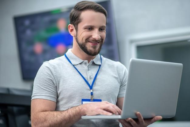 Профессионализм. радостный молодой бородатый мужчина в серой футболке со значком работает на ноутбуке, стоя в офисе