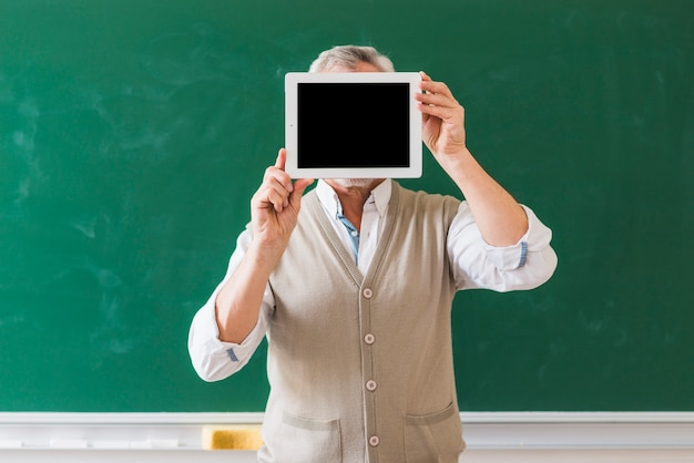 Professor showing blank space on tablet in classroom