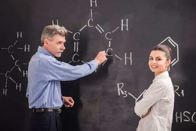 Professor and woman writes on blackboard formula together.