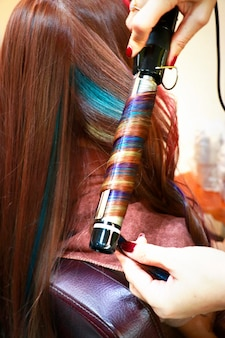 A professtional hairdressing is ironing multicolored hair and look like spiral rainbow