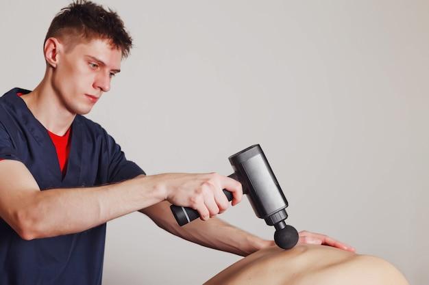 Профессиональное использование массажного пистолета на спине мужчины на белом фоне