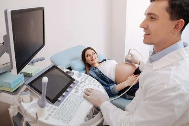 Опытный восхитительный харизматичный практикующий врач, работающий в больнице, обеспечивая ультразвуковое обследование живота беременных и консультируя беременных.