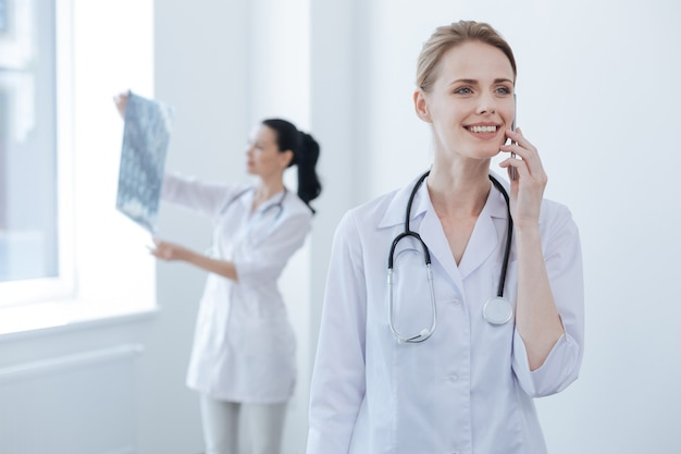 Proficient glad mature neurologist working at the medical lab and enjoying conversation on the smartphone while her colleague holding brain x ray image and analyzing it