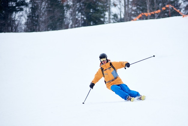 Proficient young skier concentrated on skiing down on steep ski slope